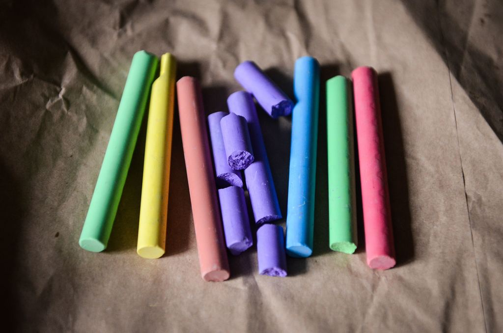 A pile of colorful chalk on a piece of butcher paper.
